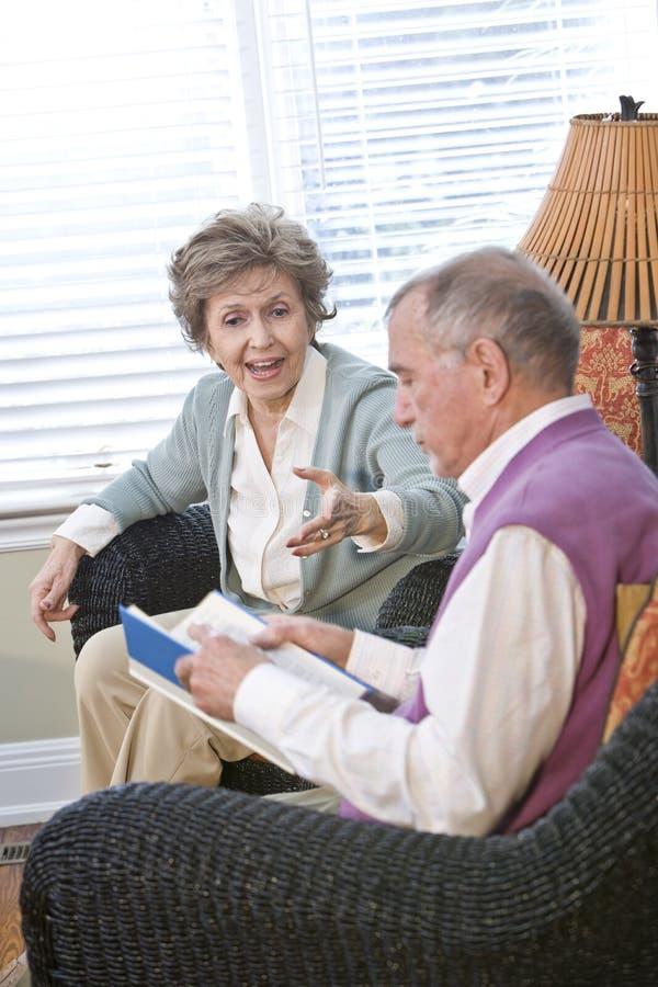 Hoger paar dat in het boek van de woonkamerlezing babbelt royalty-vrije stock foto
