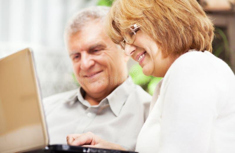 Hoger paar dat laptop met behulp van royalty-vrije stock foto's
