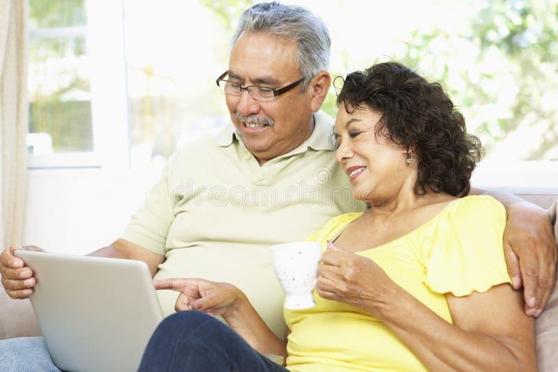 Hoger Paar dat Laptop thuis met behulp van royalty-vrije stock afbeeldingen