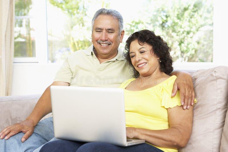 Hoger Paar dat Laptop thuis met behulp van royalty-vrije stock fotografie
