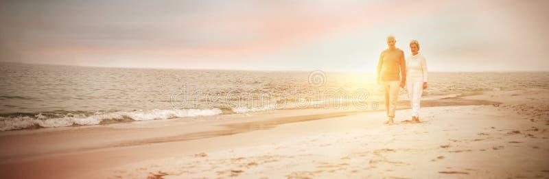 Hoger paar dat op het strand loopt royalty-vrije stock afbeeldingen