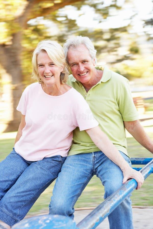 Hoger Paar dat op Rotonde in Park berijdt royalty-vrije stock foto