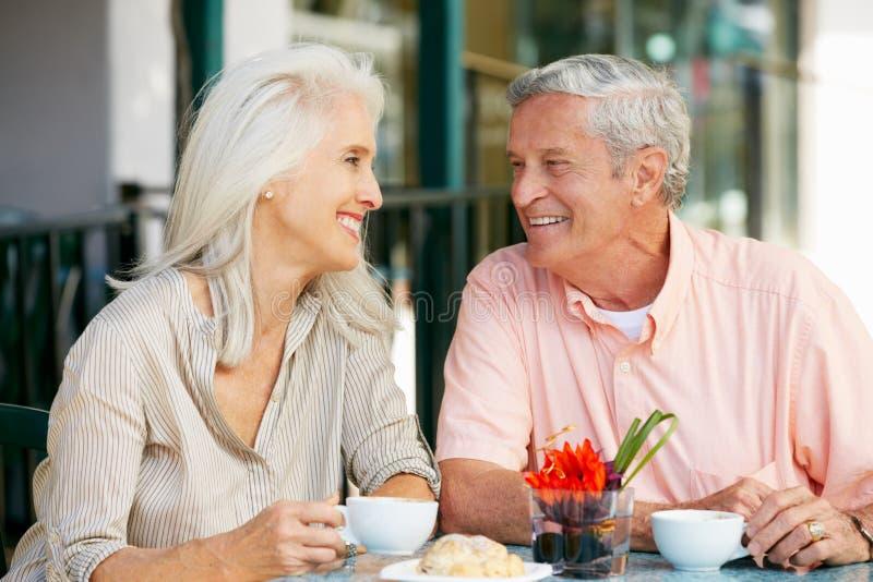 Hoger Paar dat van Snack geniet bij OpenluchtKoffie stock foto's