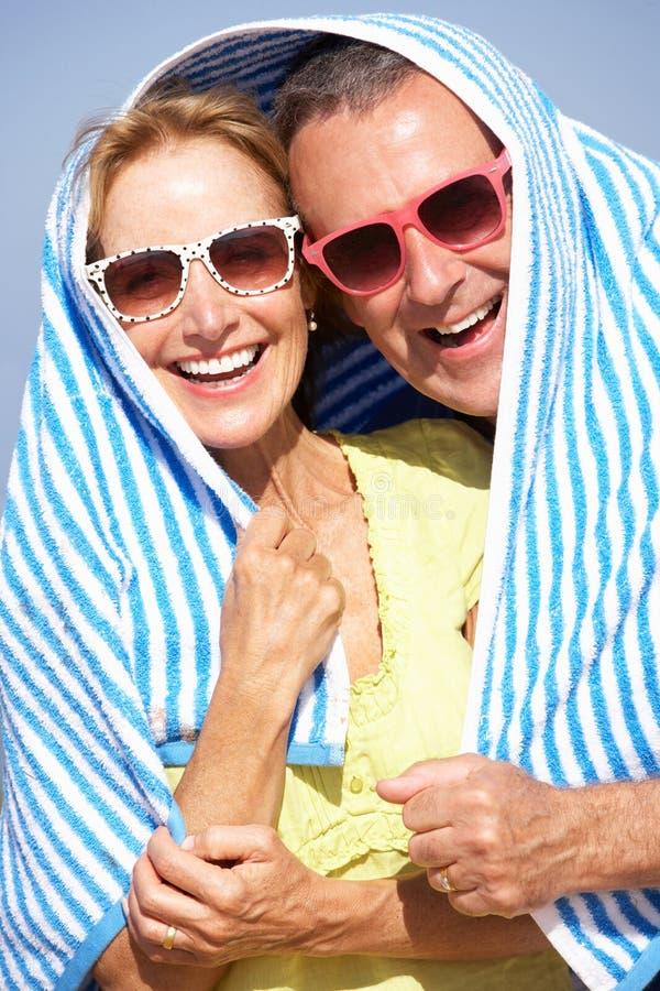 Hoger Paar dat van Zon op de Vakantie van het Strand beschut stock foto's