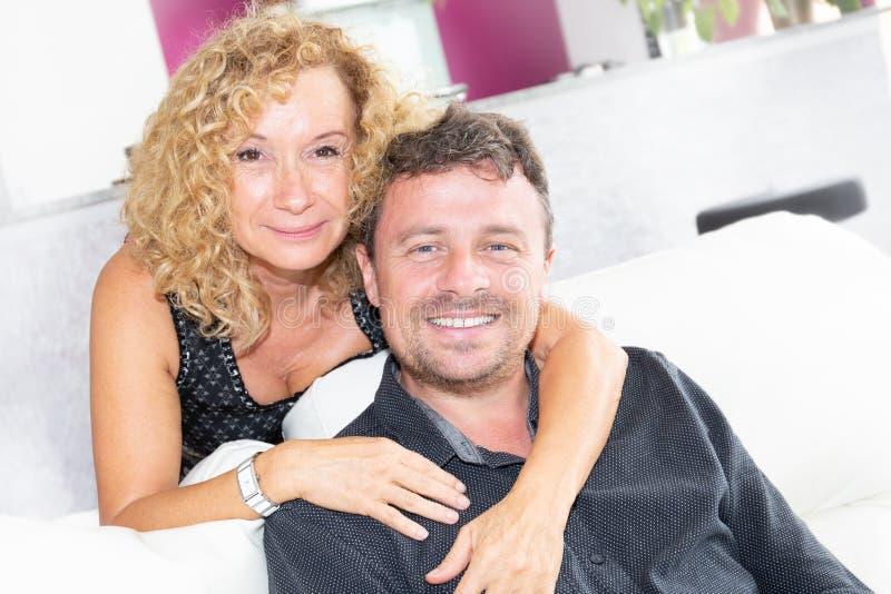 Hoger paar in de omhelzing en de liefde van de bank thuis levensstijl stock foto