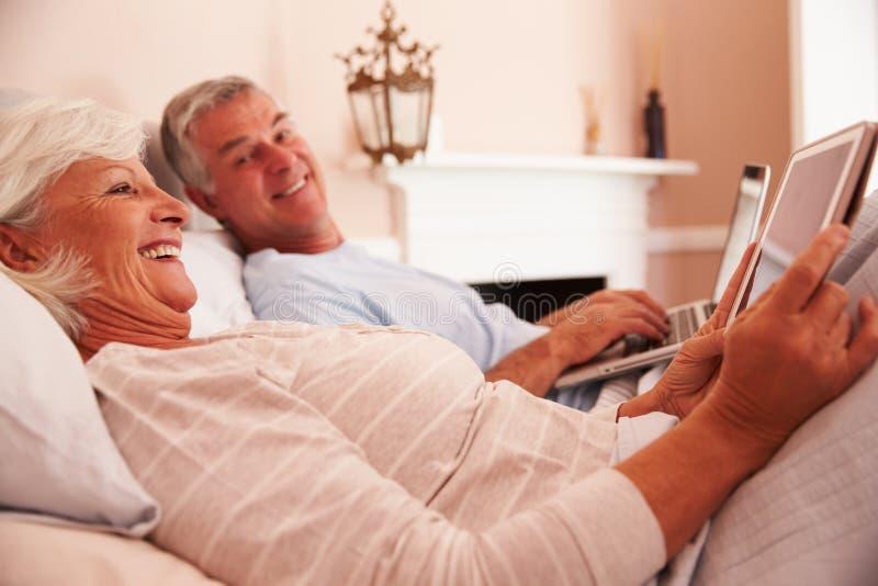 Hoger Paar die in Bed liggen die Digitale Apparaten met behulp van royalty-vrije stock afbeeldingen
