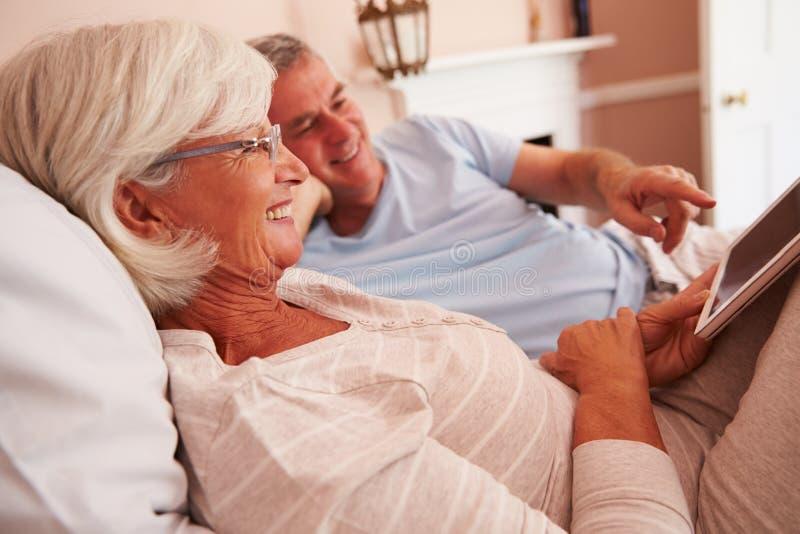 Hoger Paar die in Bed liggen die Digitale Tablet bekijken royalty-vrije stock afbeelding