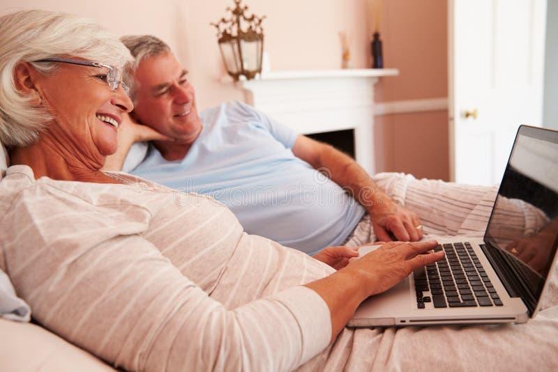 Hoger Paar die in Bed liggen die Laptop Computer bekijken royalty-vrije stock foto's