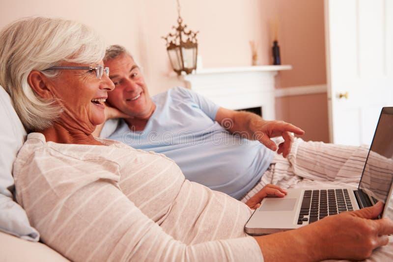 Hoger Paar die in Bed liggen die Laptop Computer bekijken stock foto