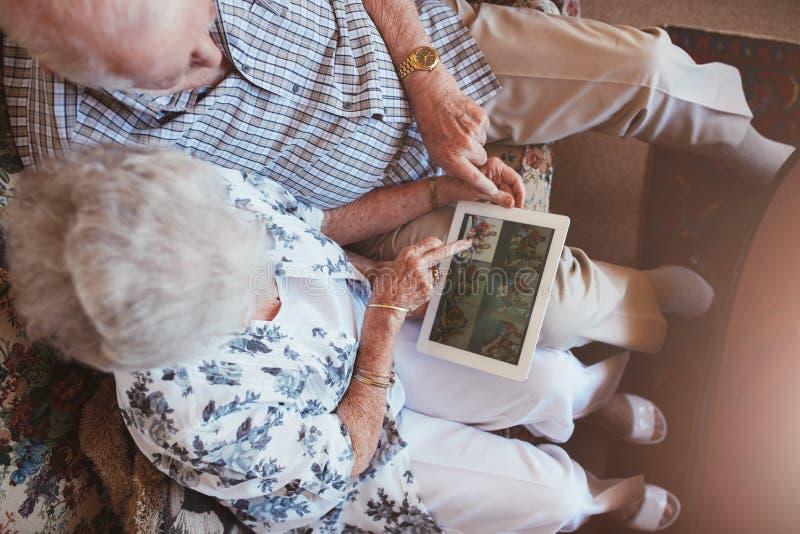 Hoger paar die beelden op digitale tablet kijken royalty-vrije stock foto