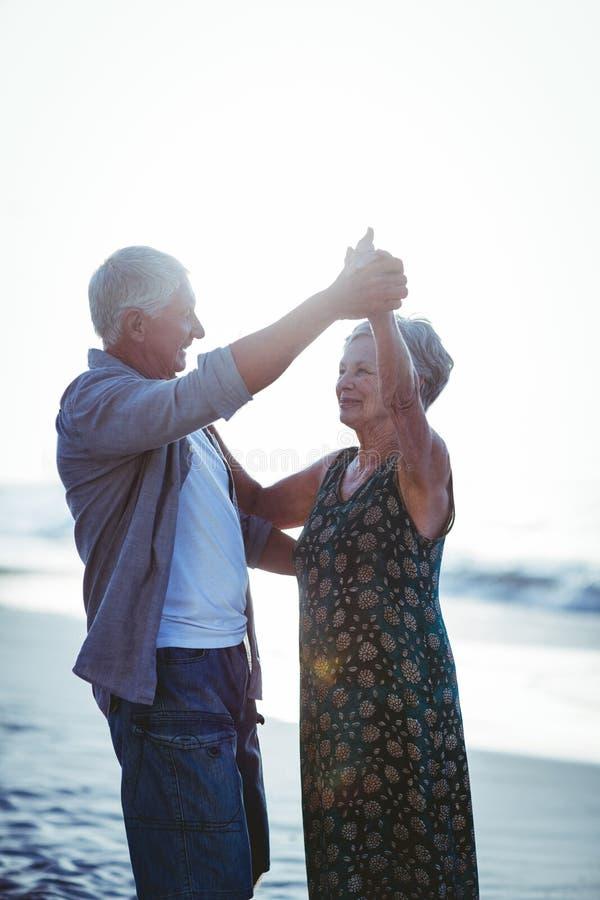 Hoger paar die bij het strand dansen stock foto