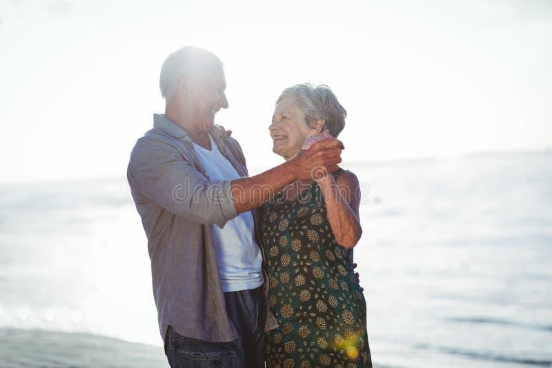 Hoger paar die bij het strand dansen stock fotografie