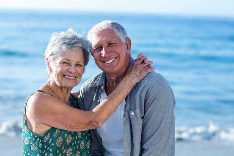 Hoger paar die bij het strand omhelzen royalty-vrije stock afbeelding