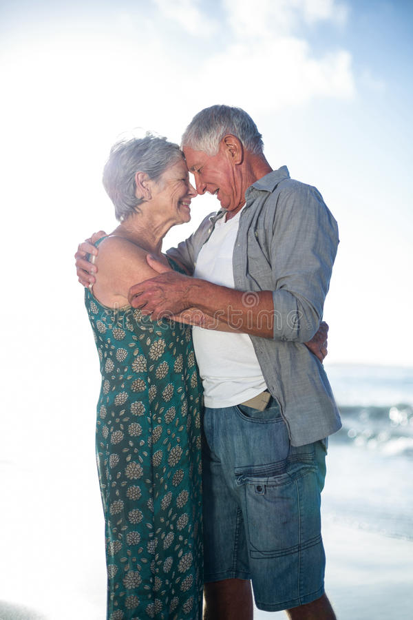 Hoger paar die bij het strand omhelzen royalty-vrije stock afbeeldingen