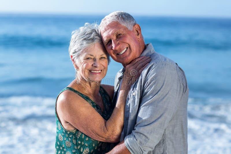 Hoger paar die bij het strand omhelzen stock afbeelding
