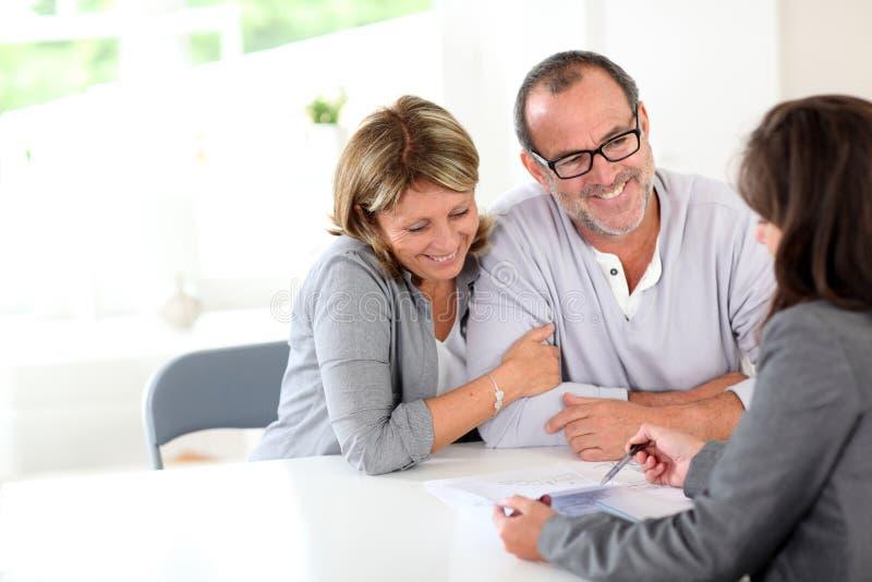 Hoger paar die contract met financiële adviseur ondertekenen stock afbeelding