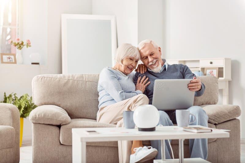 Hoger paar die door foto's van hun kleinkinderen op laptop kijken stock foto's