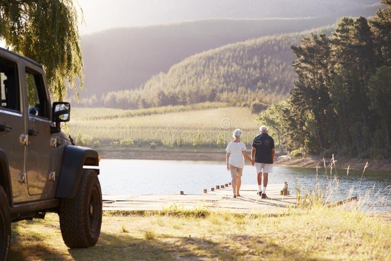 Hoger Paar die door Meer aan het eind van Wegreis lopen royalty-vrije stock fotografie