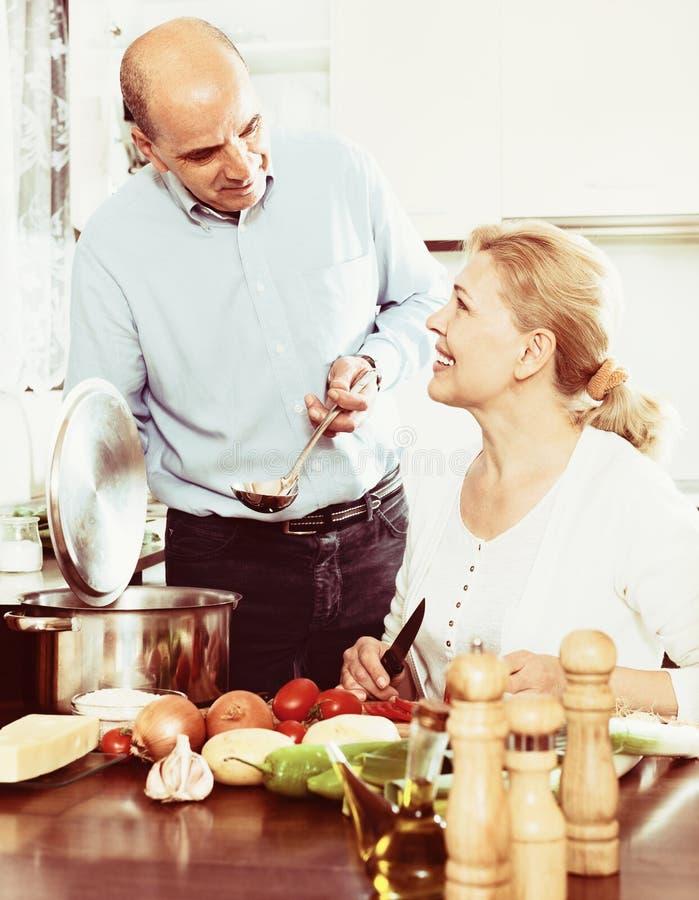 Hoger paar die een gezonde lunch in hun keuken voorbereiden royalty-vrije stock fotografie