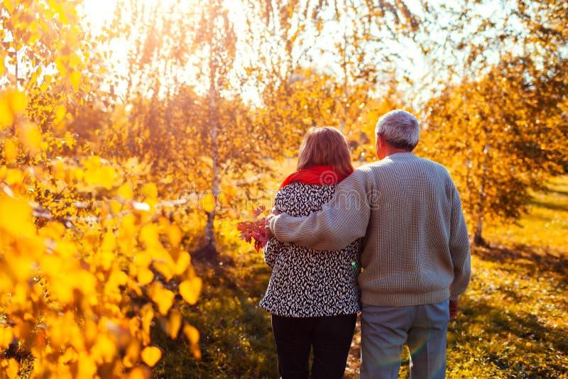Hoger paar die in en de de herfst bosmens en vrouw lopen die Op middelbare leeftijd in openlucht koesteren koelen royalty-vrije stock afbeelding