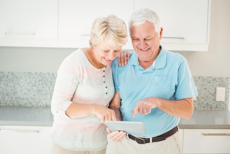 Hoger paar die gebruikend tablet in keuken lachen stock foto