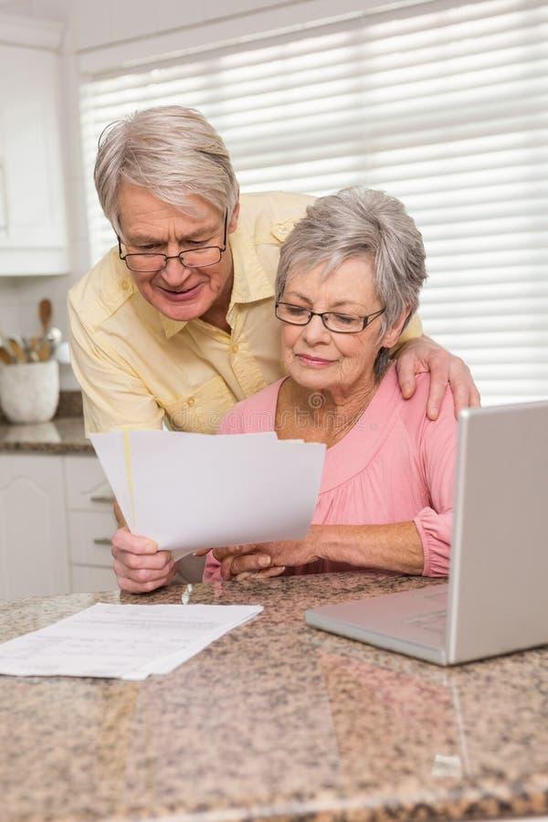 Hoger paar die hun rekeningen met laptop betalen stock afbeelding