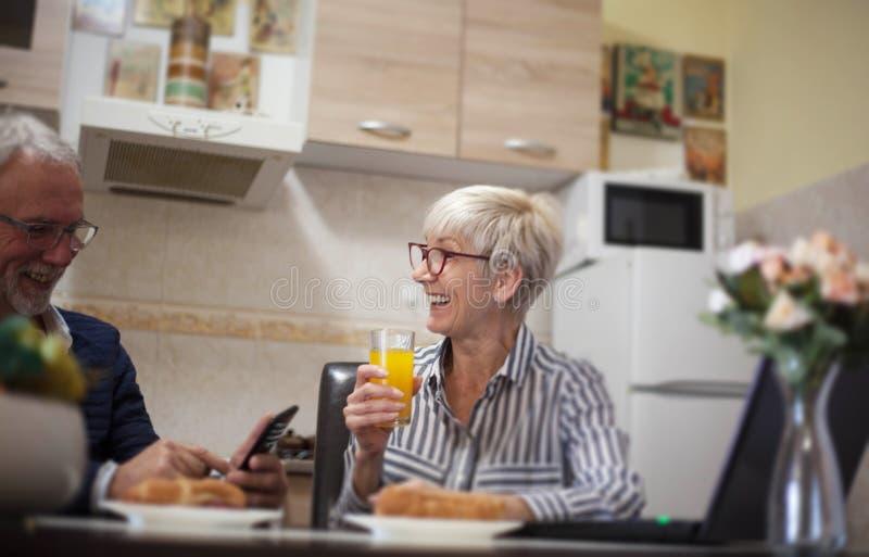 Hoger paar die in keuken lachen stock fotografie