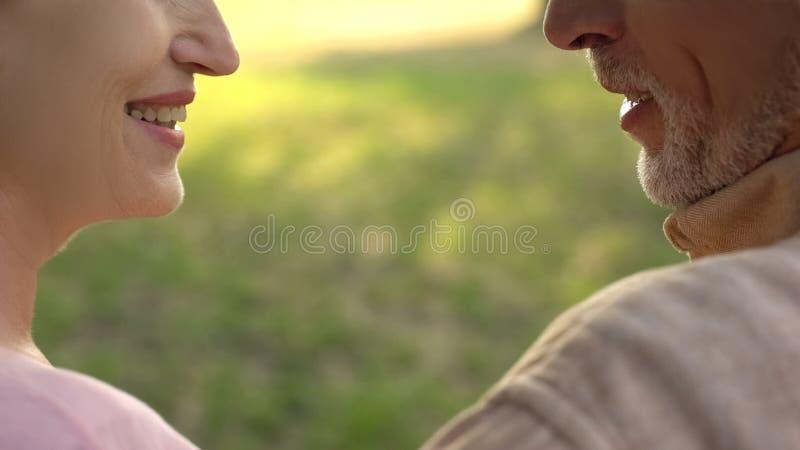 Hoger paar die in liefde elkaar, gelukkige echtgenoot glimlachen die, tederheid begrijpen stock fotografie