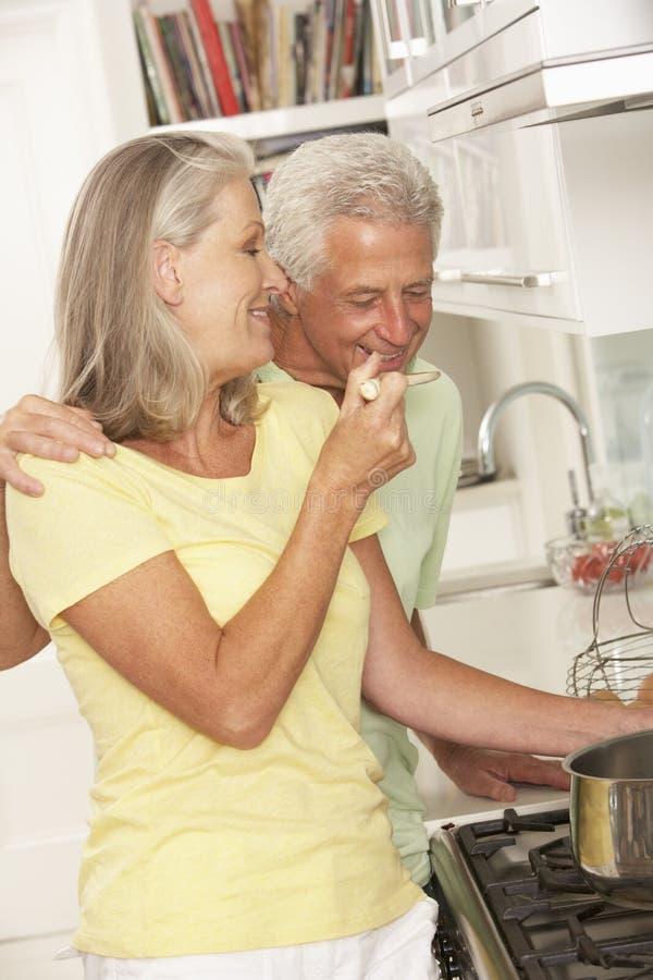 Hoger Paar die Maaltijd voorbereiden bij Kooktoestel stock foto's