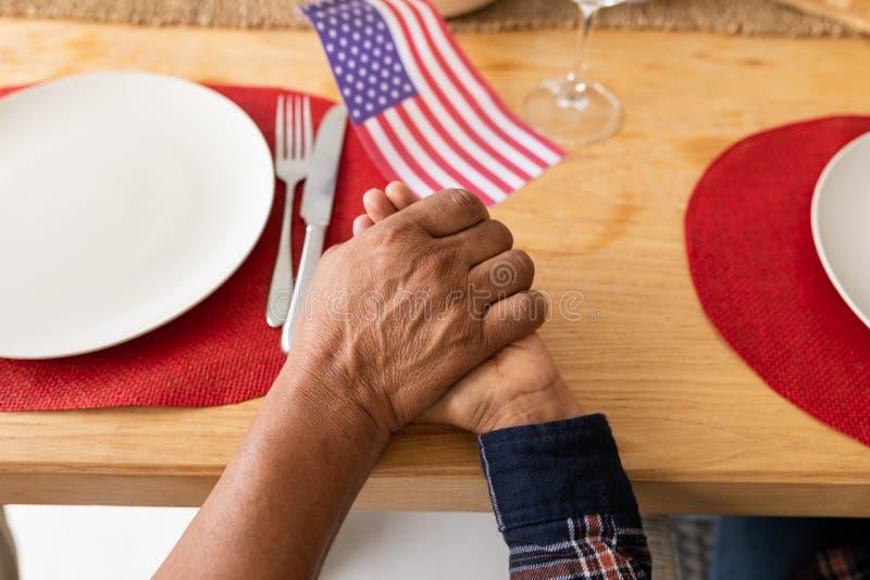 Hoger paar die met hand in hand op eettafel bidden thuis royalty-vrije stock fotografie