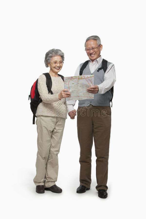 Hoger paar die met rugzakken kaart controleren stock foto's