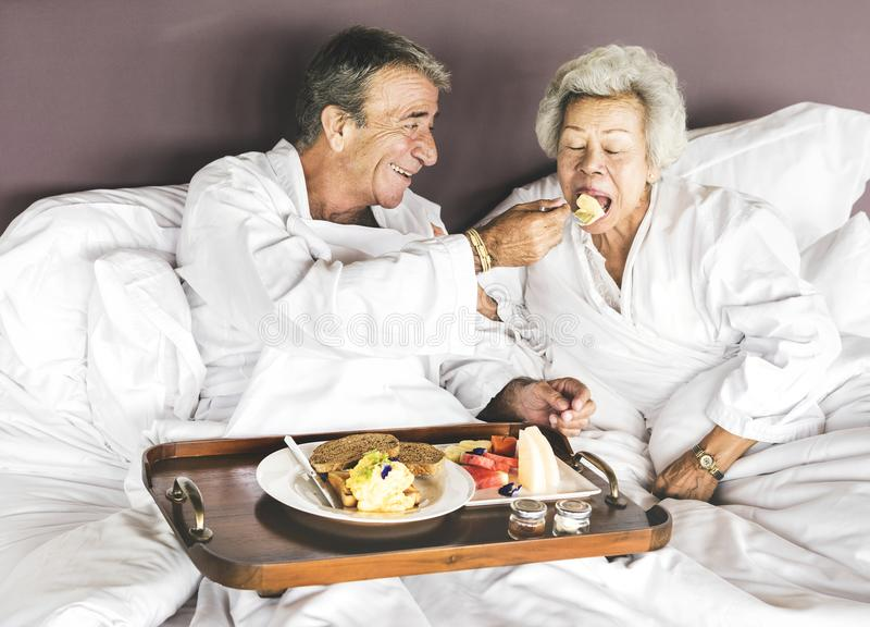 Hoger paar die ontbijt in bed hebben stock foto