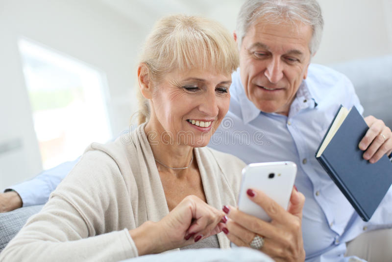Hoger paar die smartphone thuis gebruiken stock foto