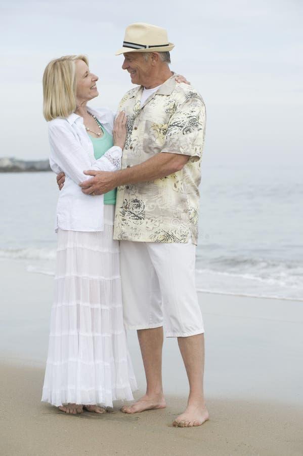 Hoger Paar die in Strand omhelzen stock fotografie