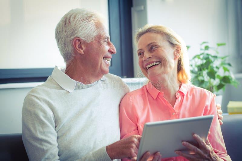 Hoger paar die terwijl het gebruiken van digitale tablet glimlachen stock foto's