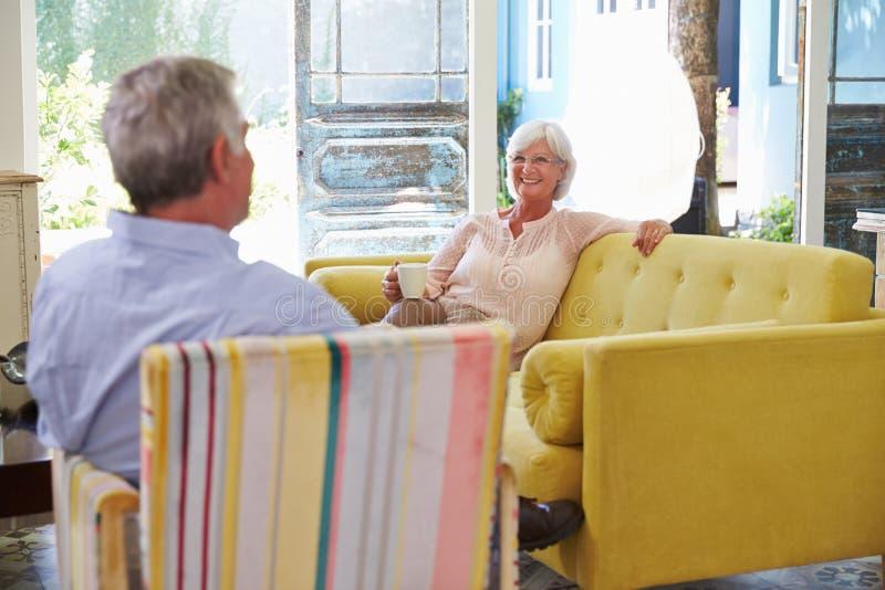 Hoger Paar die thuis in Zitkamer met Hete Drank ontspannen royalty-vrije stock fotografie