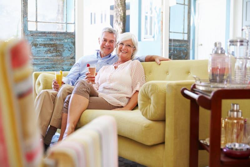 Hoger Paar die thuis in Zitkamer met Koude Dranken ontspannen royalty-vrije stock foto's