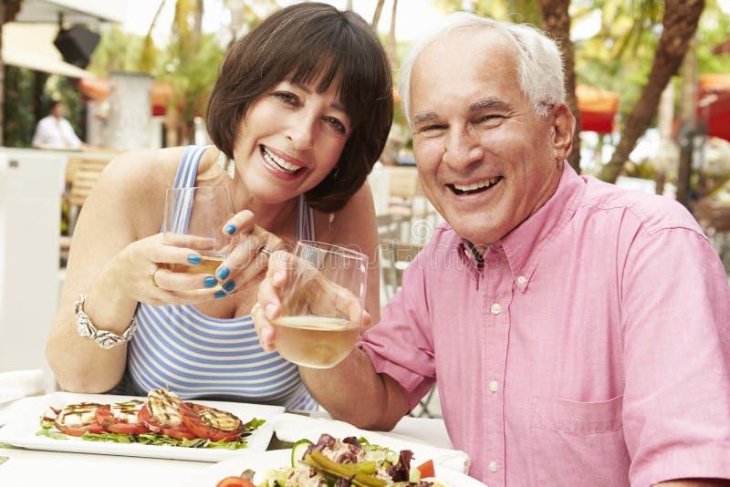 Hoger Paar die van Maaltijd in Openluchtrestaurant samen genieten royalty-vrije stock foto