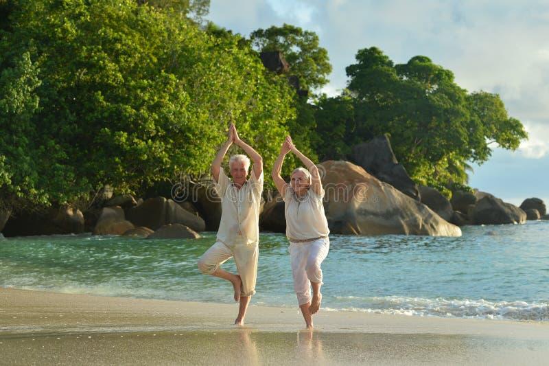 Hoger paar die yoga het uitoefenen doen stock afbeeldingen