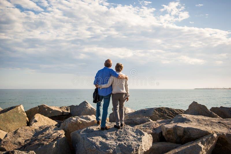 Hoger paar die zich op zonnige rotsen bevinden die van de overzeese mening genieten royalty-vrije stock foto's
