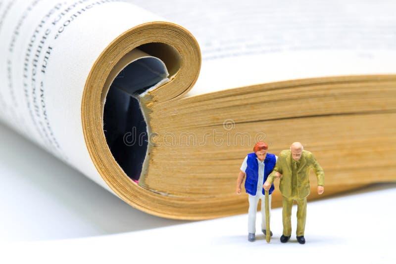 Hoger paar en open boek Lezingsmensen van hogere leeftijd Bejaard paar in de banner van het bibliotheekconcept royalty-vrije stock fotografie
