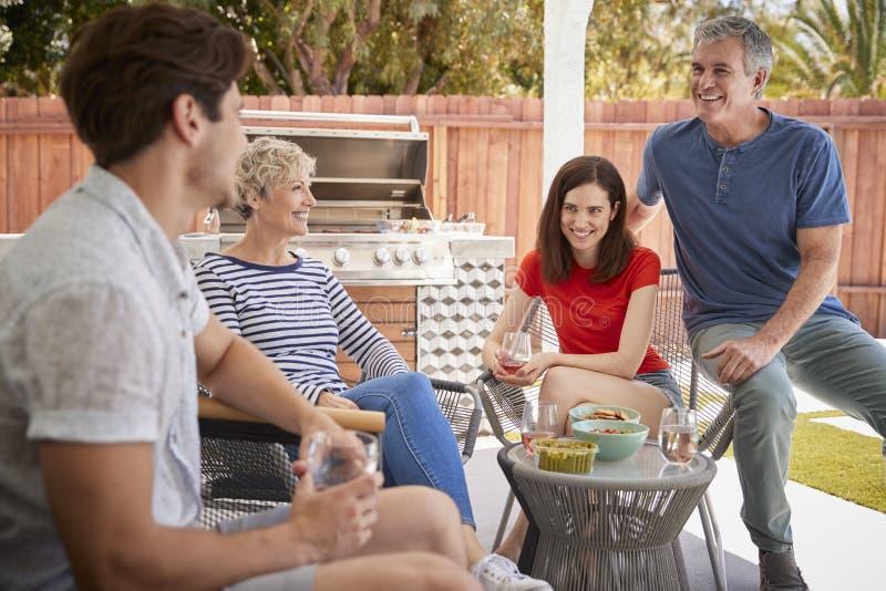 Hoger paar en volwassen kinderen op de portiek buiten huis royalty-vrije stock foto
