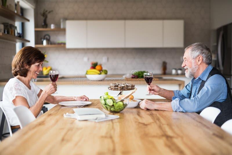 Hoger paar in liefde die lunch hebben binnen thuis, het spreken stock foto