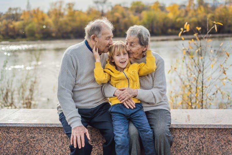 Hoger paar met babykleinzoon in het de herfstpark Groot-grootmoeder, groot-grootvader en groot-kleinzoon stock fotografie