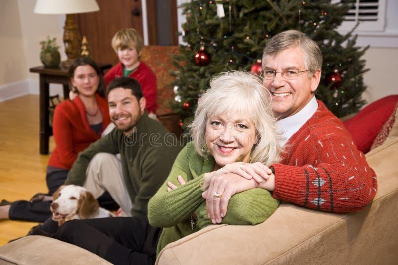 Hoger paar met familie door Kerstboom stock afbeeldingen