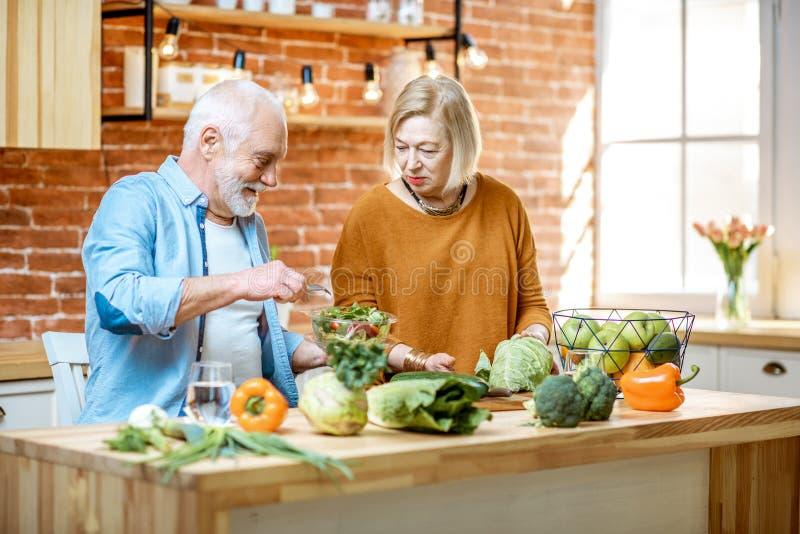 Hoger paar met gezond voedsel thuis stock fotografie