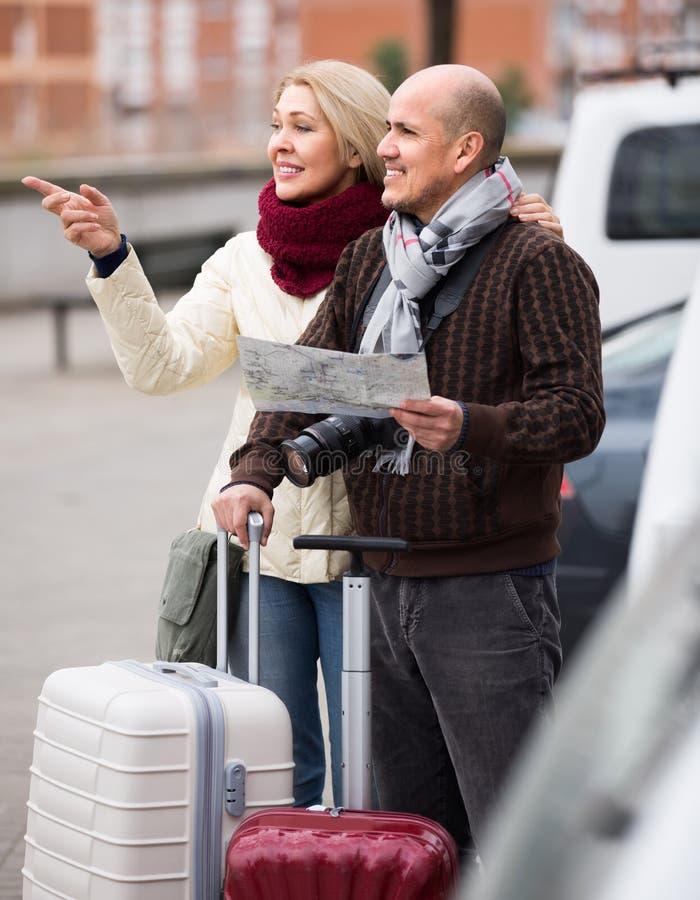 Hoger paar met kaart en bagage stock foto