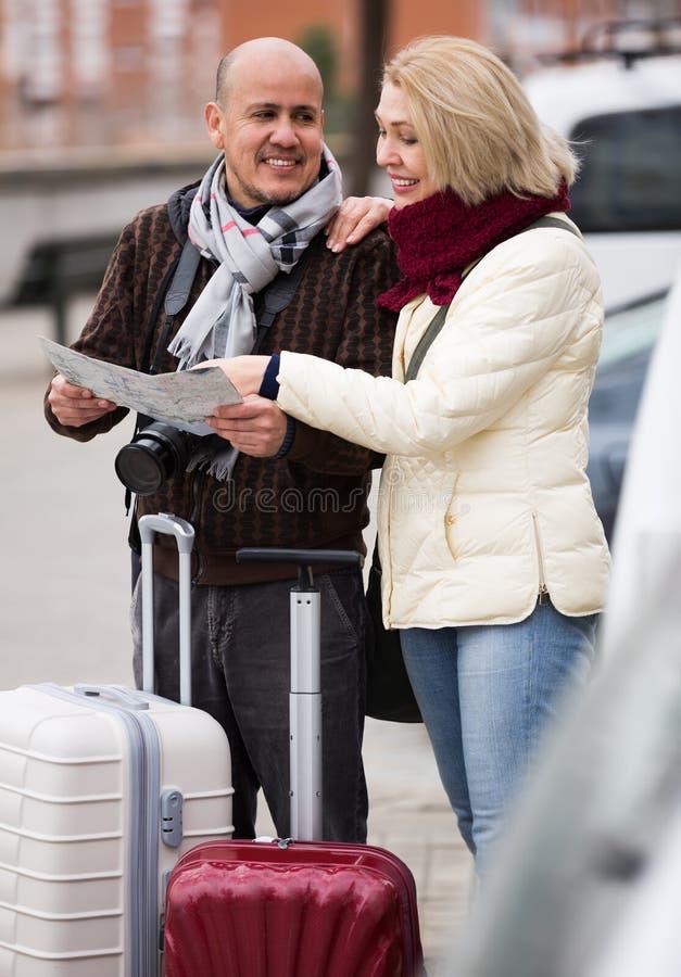 Hoger paar met kaart en bagage stock fotografie