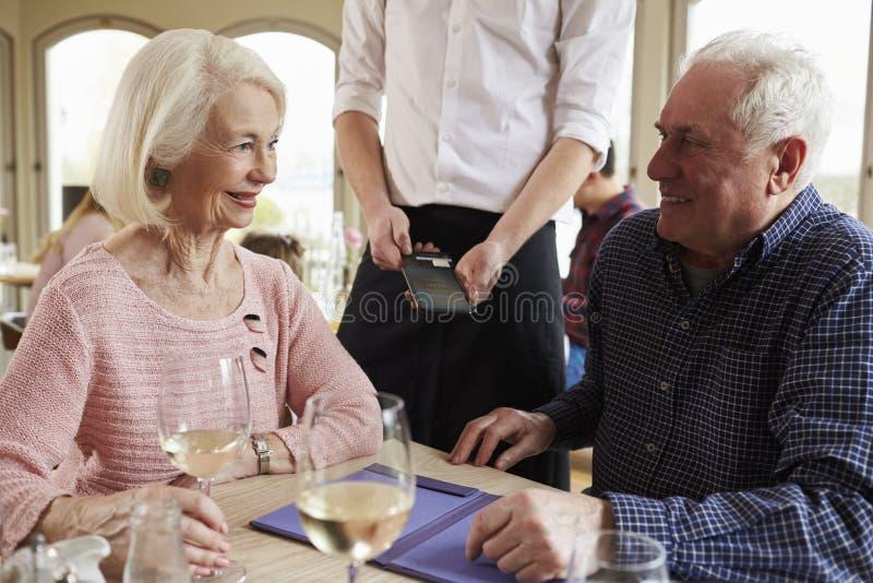 Hoger Paar met Kelner Paying Bill In Restaurant stock afbeelding