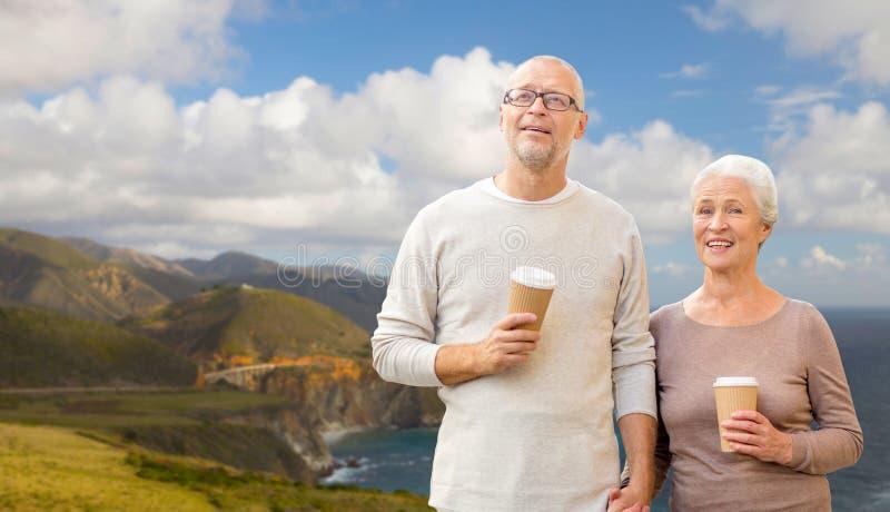 Hoger paar met koffiekoppen over grote surkust royalty-vrije stock afbeeldingen